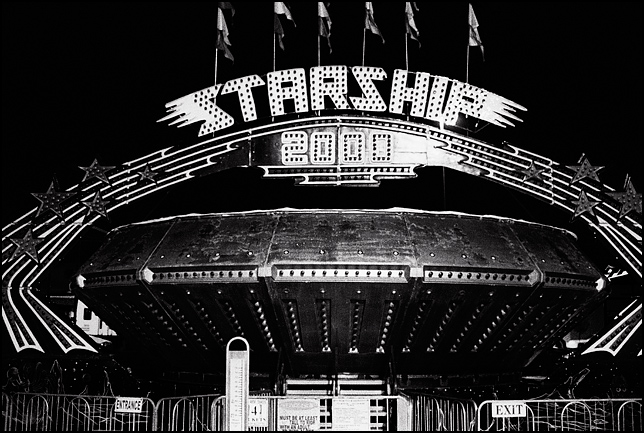 The Starship 2000 ride in a carnival at night after the midway closed. The ride looks like a spinning UFO.