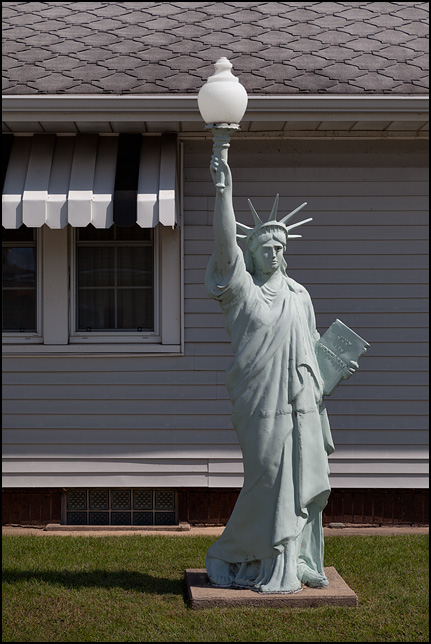 A Statue of Liberty lamp post in the front yard of a house on Beiger Street in Mishawaka, Indiana. Made of cast aluminum by Tuscumbia Iron Works.