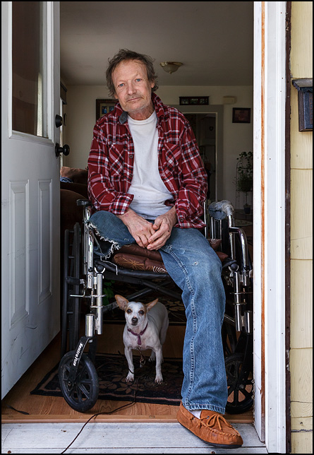 Sterling Hall Senior sitting in a wheelchair in the entrance to his house. His little white dog stands under the chair.