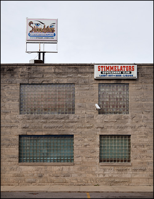 Stimmelators Gentlemans Club, a strip club in the small town of North Webster, Indiana. Stimmelators is a two story limestone building with windows made of glass bricks.