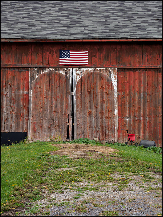 The side of an old red barn with an American flag hanging over the doors. Located behind a farmhouse on Saint Joe Road in rural Allen County, Indiana.