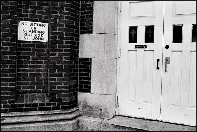 A sign on the doors of the Saint John Day Center homeless shelter in Louisville that says No Standing or sitting outside.