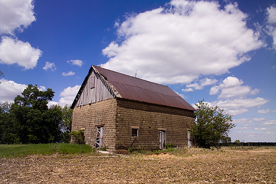 Old abandoned cinderblock barn with wood and metal roof in rural Pulaski County, Indiana. The deep blue sky is filled with dramatic fluffy white clouds. The barn sits in an overgrown lawn next to an empty cornfield.