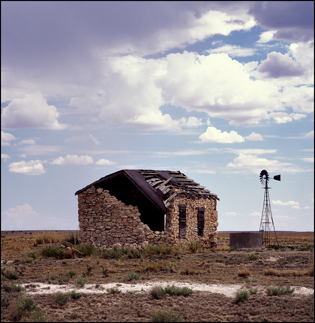 An abandoned stone house with a tin roof sits on a ranch in the New Mexico desert along US-55 south of Santa Rosa. A windmill and water tank stand next to the crumbling home and dark storm clouds gather in the sky above.