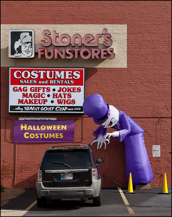 An inflatable monster, based on an air dancer or tube man, attacks a car parked behind Stoners Funstore in Fort Wayne, Indiana.