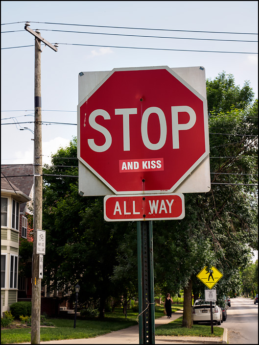 A stop sign on the corner of Pennsylvania Road and 25th Street in Indianapolis. It has a sticker that makes the sign say Stop And Kiss.