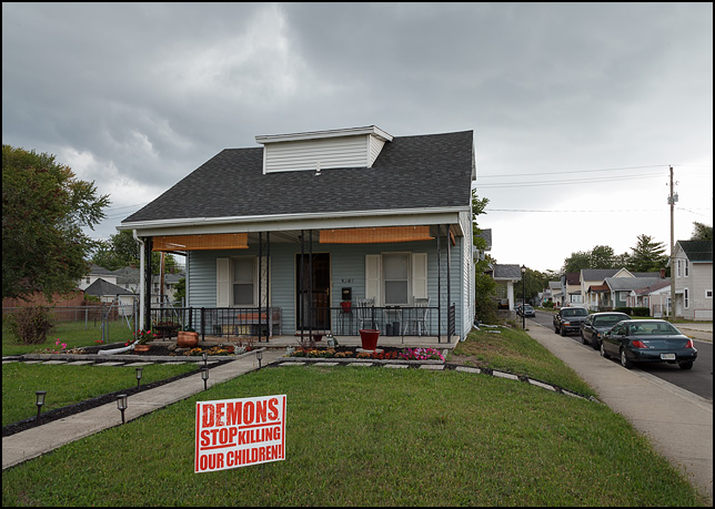 A sign that says Demons Stop Killing Our Children. The sign is in the front yard of a house on Lafayette Street in the inner-city in Fort Wayne, Indiana. Dark storm clouds fill the sky above the small blue house.