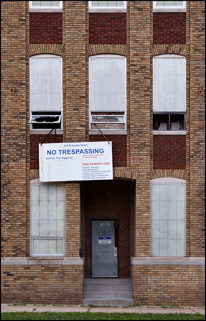 A vacant warehouse on Jacobs Avenue in Fort Wayne, Indiana. A sign above the door says No Trespassing and offers a $500 reward for information about the vandals who keep tagging the brick building with graffiti.