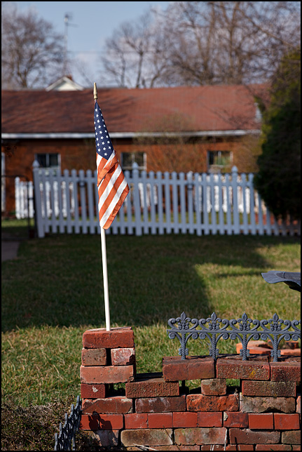 A small American flag on a little brick wall in a flowerbed next to a house on Stophlet Street in Fort Wayne, Indiana.