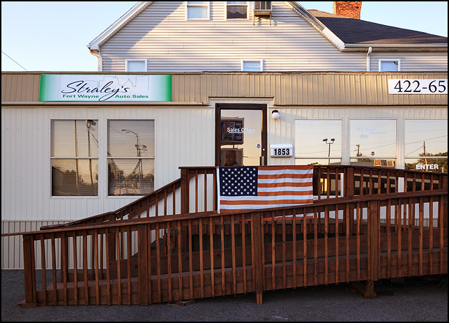 An American flag hanging on the front of the office trailer at Straley's Fort Wayne Auto Sales, a used car dealer on Broadway in Fort Wayne, Indiana.