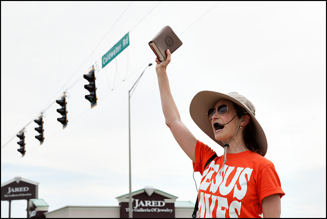 A female street preacher wearing a Jesus Saves t-shirt and a bullhorn holds a bible in the air at the corner of Coliseum Boulevard and Coldwater Road in Fort Wayne, Indiana.