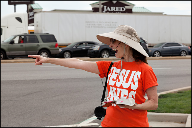 A female street preacher wearing a Jesus Saves t-shirt points and yells to a driver at the corner of Coliseum Boulevard and Coldwater Road in Fort Wayne, Indiana.