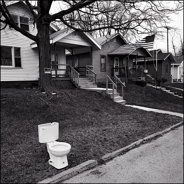 A toilet left out for the garbage collection sits on the curb in front of a house in Fort Wayne, Indiana. An American flag flies in front of another house in the distance.