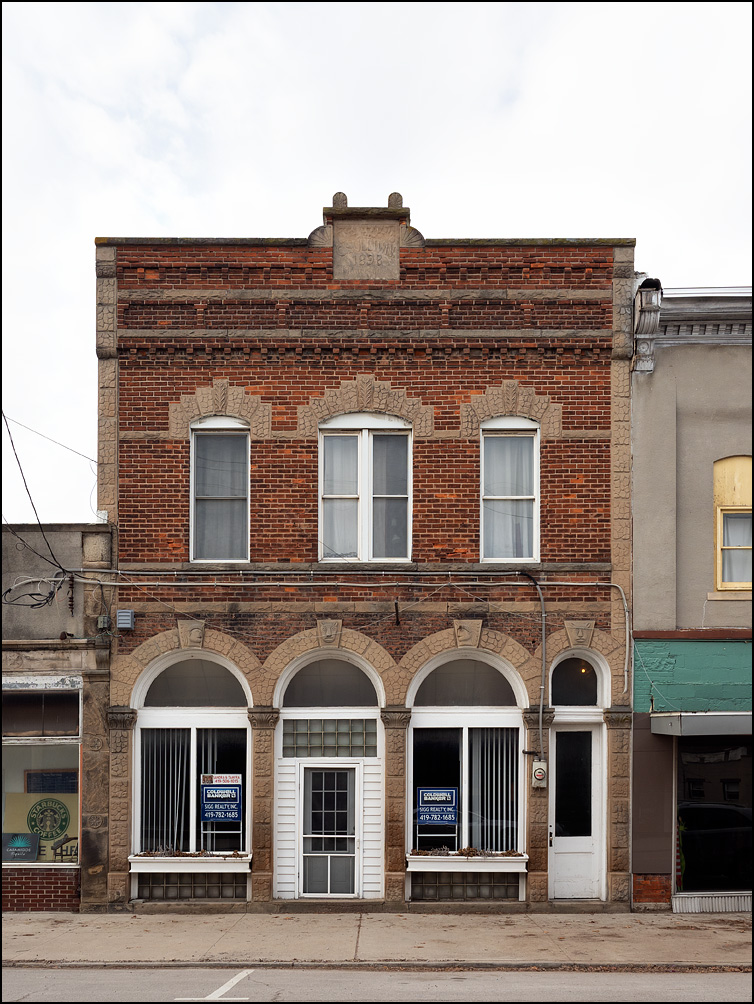 The C. Sullivan Building on Main Street in the small town of Antwerp, Ohio. The two story brick building has arched windows on the first floor storefront.