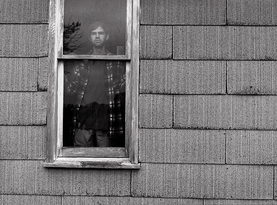 Self portrait of fine art photographer Christopher Crawford in the window of an abandoned farm house.