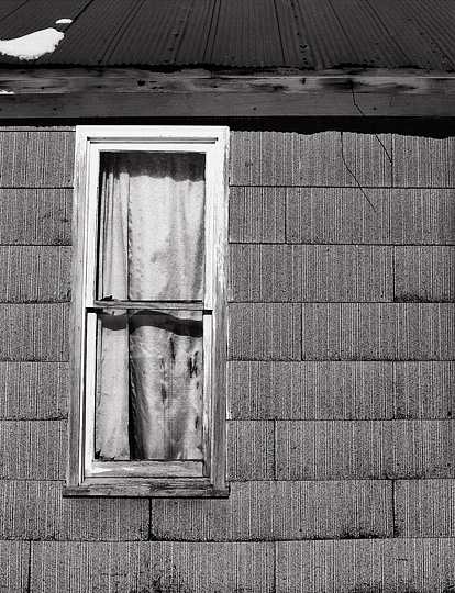 Curtains hang in a window on the side of an abandoned summer kitchen on Winters Road in Allen County, Indiana.