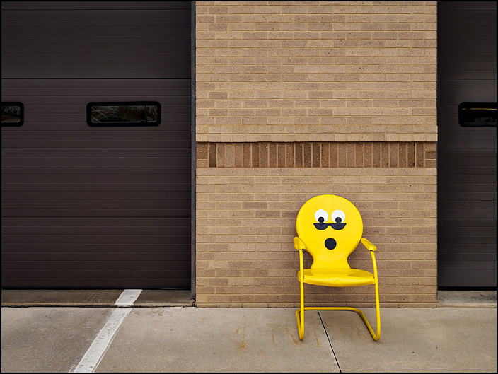 A yellow metal motel chair with an emoji face wearing sunglasses painted on it sits in front of Fire Station 10 at the corner of Crescent and Anthony in Fort Wayne, Indiana.