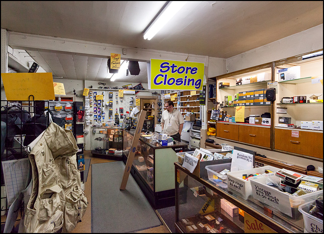 Salesman Andrew Christie stands behind the counter at Sunny Schick Camera Shop during their going out of business sale.