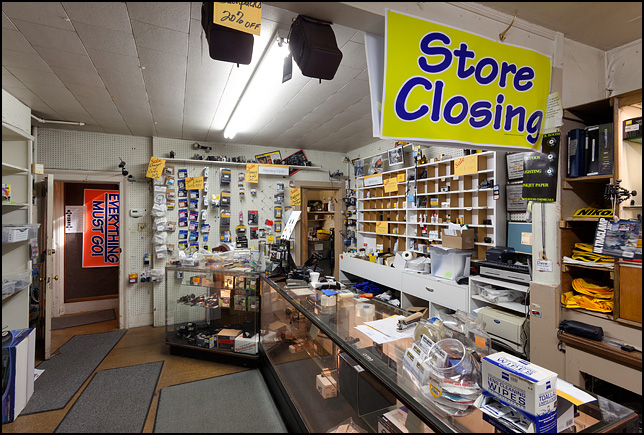 The shelves and counters at Sunny Schick Camera Shop are nearly empty during their going out of business sale. Signs say, Everything Must Go and Going Out Of Business.