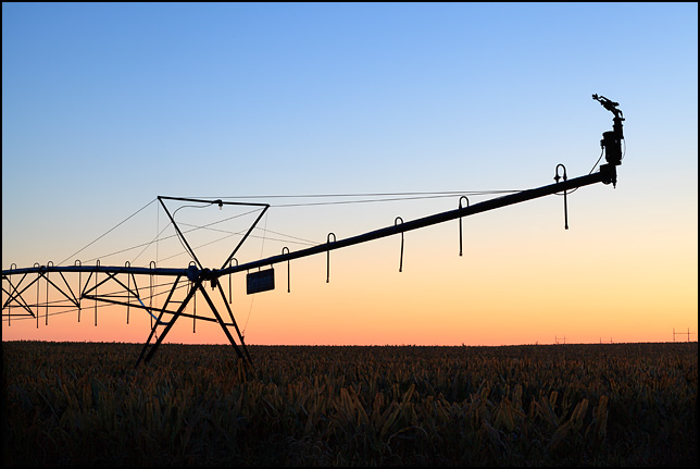 An irrigation sprayer silhouetted against the sky at sunrise on a farm in rural Elkhart County, Indiana.