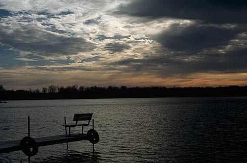 A bench on the end of a pier under a dark sunset sky at Goose Lake in Whitley County, Indiana.