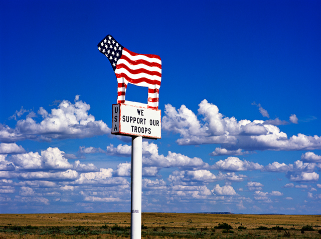 This cow shaped sign painted like the American flag stands along Interstate 40 in Quay County, New Mexico. It says We Support Our Troops USA.