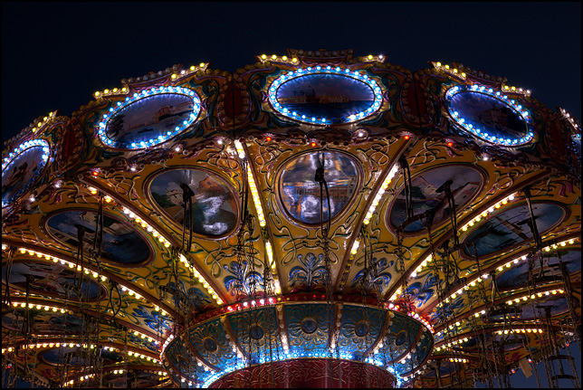 The bright lights on the Swing Carousel ride shine in the darkness at the Three Rivers Festival carnival in Fort Wayne, Indiana.