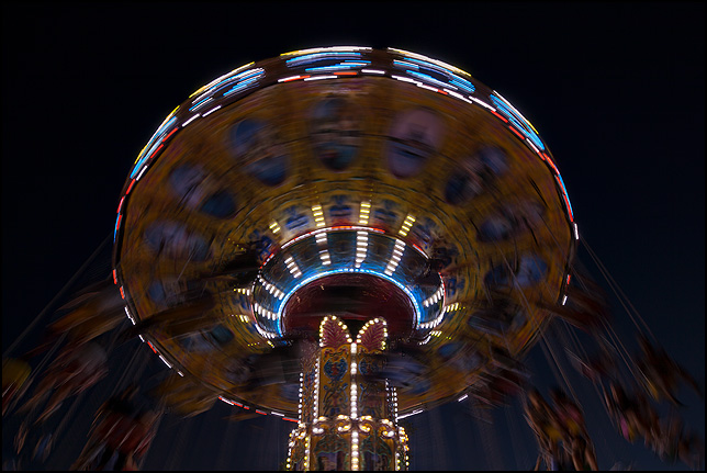 The Swing Carousel ride spins rapidly, forming a blur of colorful light in the dark sky at the Three Rivers Festival carnival in Fort Wayne, Indiana.
