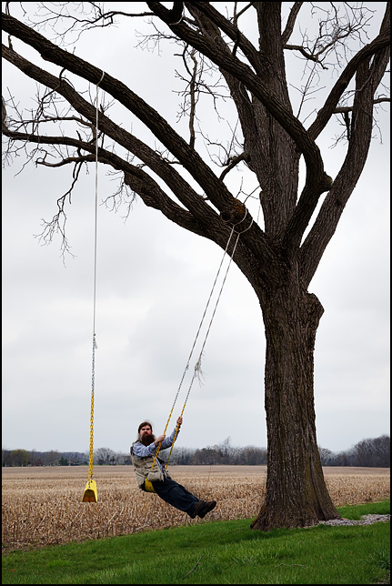 Self-portrait of photographer Christopher Crawford swing on a tree swing in rural Indiana.