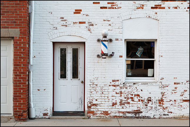 The front window of a barbershop in a whitewashed brick building on Pearl Street in the small town of Syracuse, Indiana. A barber pole hangs next to the door of the shop, which is closed.