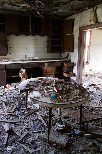 A dining room table stands in the middle of the kitchen of an abandoned farmhouse. Broken plaster and wood litters the floor and all the cabinets and drawers in the kitchen look ransacked.