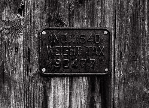 A rusty metal 1940 Indiana Weight Tax compliance sign on a weathered wood barn door at an abandoned farm.