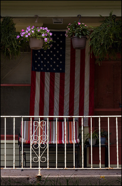 A large American flag and several flower pots hang on the front porch of an old house on Taylor Street in Fort Wayne, Indiana.