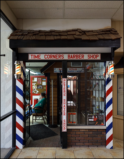Two small barber poles flank the entrance to Time Corners Barber Shop at Westland Mall in Fort Wayne. The wrought iron gate that serves as the door is open and a customer can be seen inside waiting to get his hair cut.