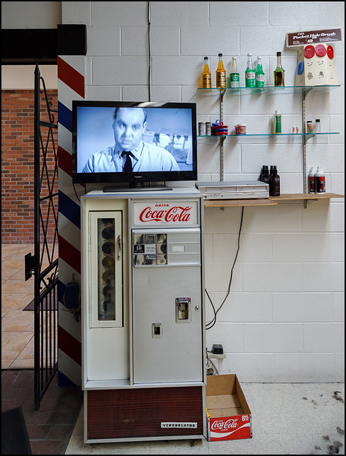 An ancient Vendorlator Coca-Cola machine that sells old-fashioned glass bottles in a barber shop. A television showing an old black and white movie sits on top of the Coke machine, and bottles of hair care products are displayed on shelves next to it.