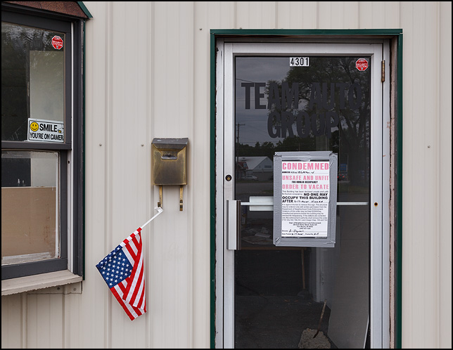 A condemnation notice from the city government is taped to the front door of Team Auto Group, a used car lot on Bluffton Road in Fort Wayne, Indiana. A car-window American flag hangs upside-down from the mailbox next to the door.