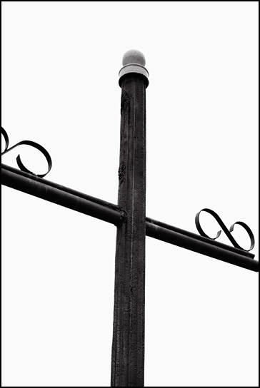 Steel crucifix with fancy iron scrollwork in the churchyard outside the Catholic church in Tecolote, New Mexico.