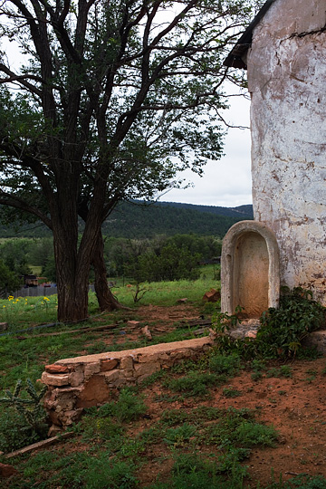 An empty shrine that once held a statue of the Virgin Mary stands next to an abandoned adobe house in Tecolote, New Mexico.