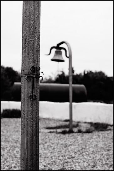 Small metal cross tied to a pole in front of a church in Tecolote, New Mexico. A bell stands on a pole in the background.