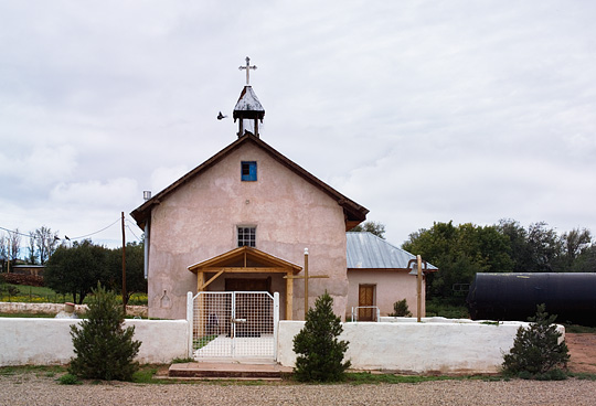 The old adobe church in the mountain village of Tecolote, New Mexico with pigeons flying near the steeple. The church is surrounded by an adobe wall and a large cross and a pole with a bell stand in the churchyard.