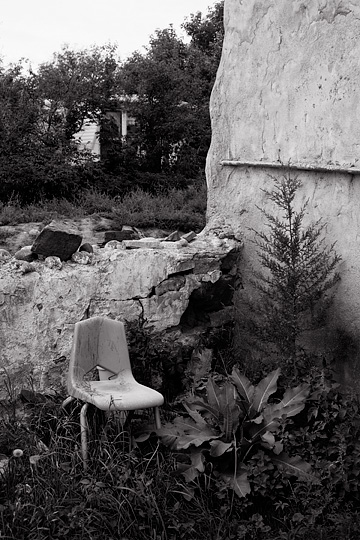 Tall weeds surround an old plastic school chair behind the church in Tecolote, New Mexico. The chair sits in front of the stone wall around the churchyard.