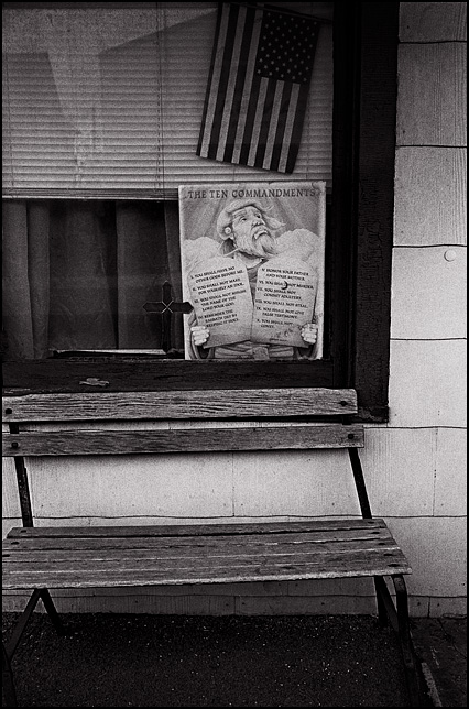 A poster with the Ten Commandments hangs under an American flag with a crucifix in the front window of an old house on Wells Street in Fort Wayne, Indiana. An old wooden park bench sits on the porch under the window.