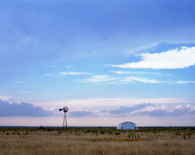 Beautiful sunset over a quanset hut and windmill on the plains of the Texas panhandle east of Amarillo.
