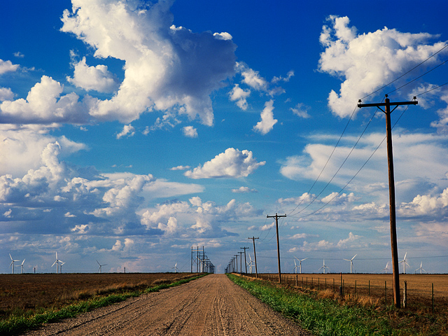Everett Road stretches into the distance toward a wind farm under a cloud filled blue sky in Oldham County, Texas.