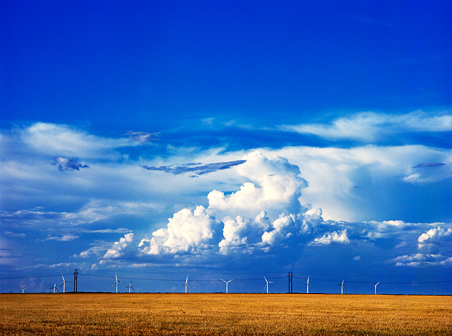 Windmills stand under a big blue sky and huge white clouds on a farm in Vega, Texas.