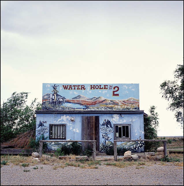 Water Hole #2 is an abandoned bar on Route 66 in Texola, Oklahoma. The adobe building has an old west mural painted across the front of it.