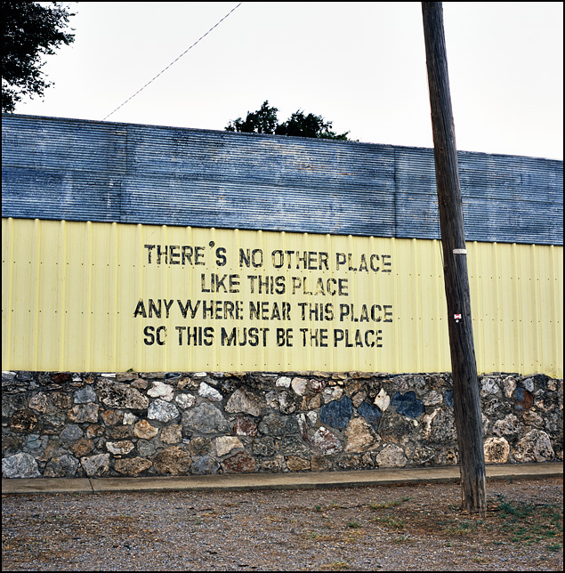 This poem is written on the front of a bar in Texola, Oklahoma. There's no other place like this place anywhere near this place so this must be the place.