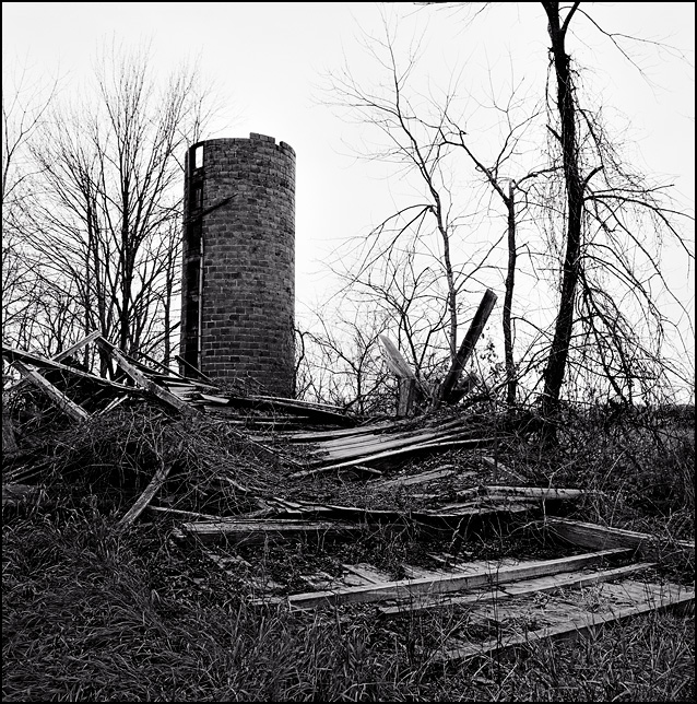 An old brick silo stands in the middle of a pile of wooden beams from a barn that collapsed on an abandoned farm on Thiele Road in Allen County, Indiana.
