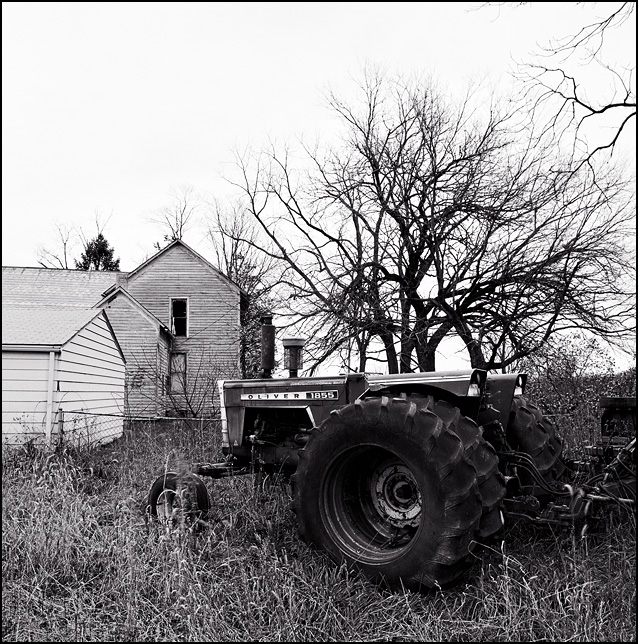 An old Oliver 1855 farm tractor surrounded by overgrown weeds behind an abandoned farmhouse on Thiele Road in Allen County, Indiana.