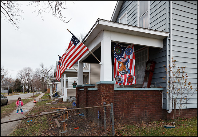 A house with three American flags on the porch. One has the insignia of all the branches of the US Military and the POW-MIA flag on it.